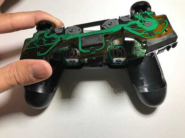 Remove the top layer PCB. The PCB must be popped out of place and then angled in such a way that the trigger buttons at the top of the controller slide out of their slots.