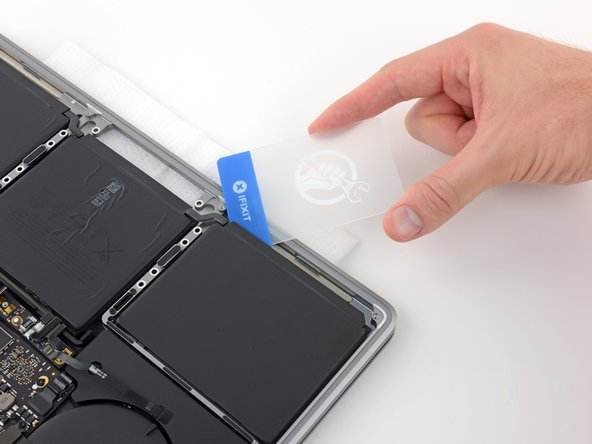 After 2-3 minutes have passed, slide a plastic card under the edge of the battery cell where you applied the adhesive remover.