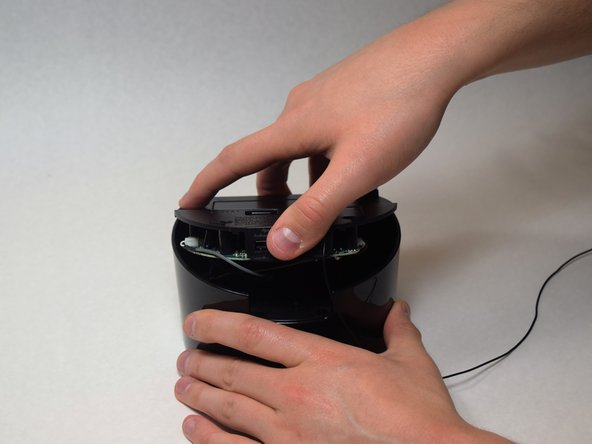 Grip the top of the iBT230 by placing your thumb on the back portion, where the USB port is located. Pull up, and you should notice various different colored wires, connected to the Main Motherboard.