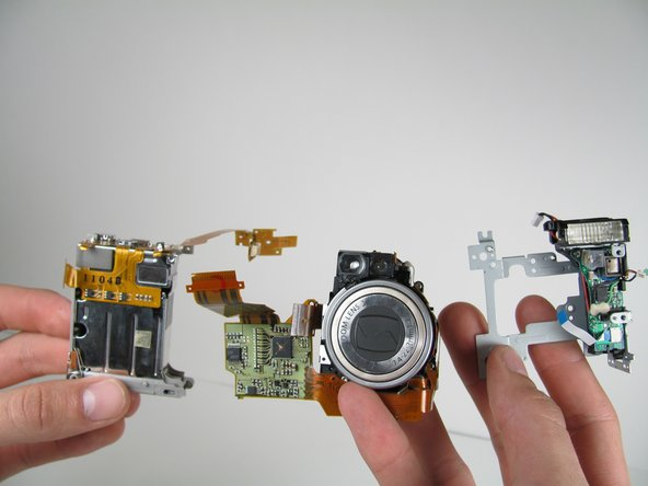 The remaining pieces from left to right are: the battery casing, zoom lens and flash assembly.