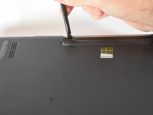 Remove the top and middle rubber feet under the laptop to reveal hidden screws.
