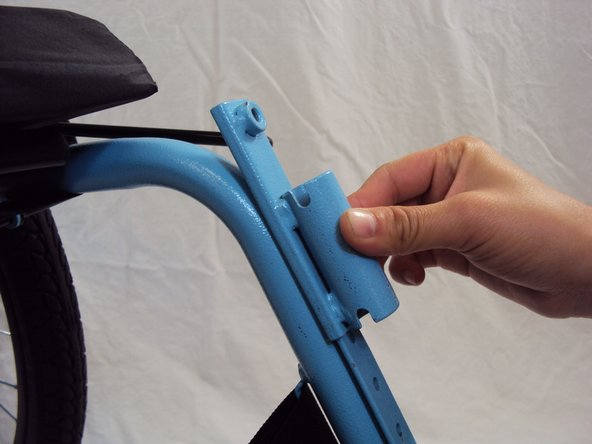 Slide the footrest sockets down as shown and use a 10 mm wrench to tighten the bolts at the desired height.