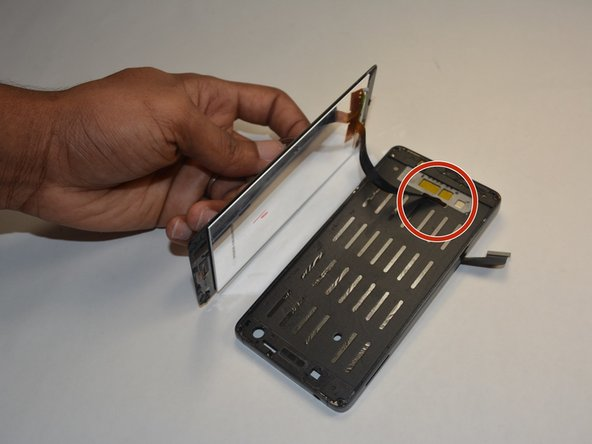 Once you have pulled the screen completely off the device, there will be a ribbon wire that you previously detached from the motherboard that can be pulled gently through a hole.