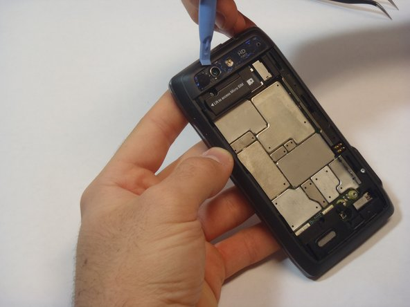 Using the blue plastic opening tool, pry off the thin plastic camera cover.