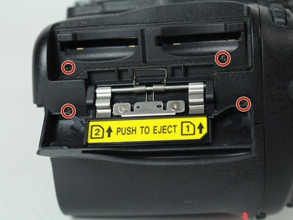 Remove four 6 mm J000 screws that secure the SD card cover.