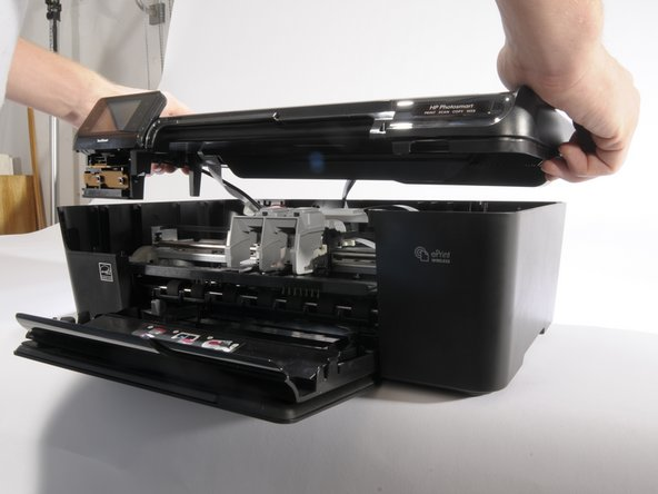 This step is easier with two people. Carefully have one person lift the hood of the printer 2-3 inches above where it was resting.