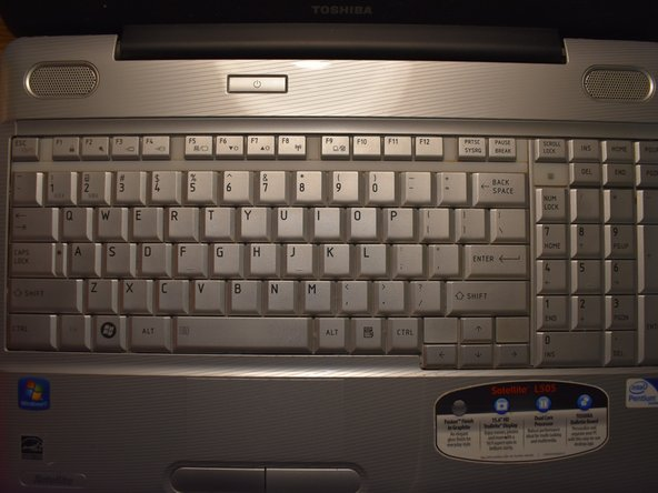 Open the laptop and locate the plastic strip just above the keyboard.
