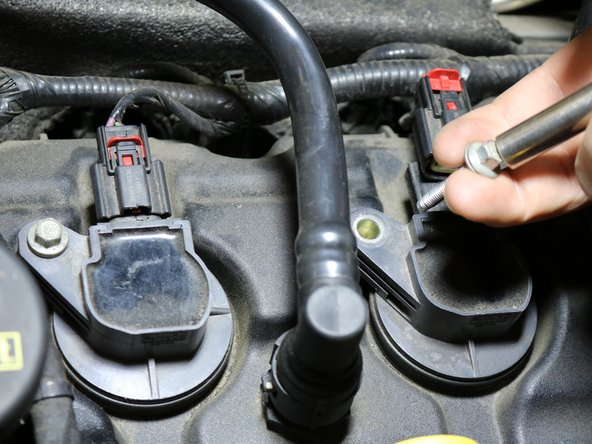 """Remove the 10mm screw from the coil pack. Use the 10mm socket on the 3/8"""" drive ratchet to remove the screw."""