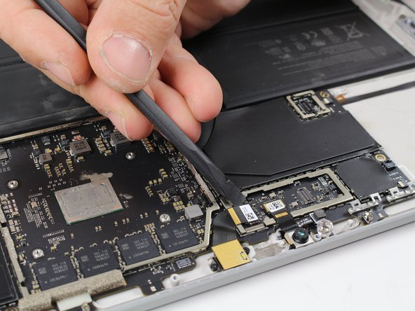 Lift the rear camera ribbon cable off the motherboard using the nylon spudger.