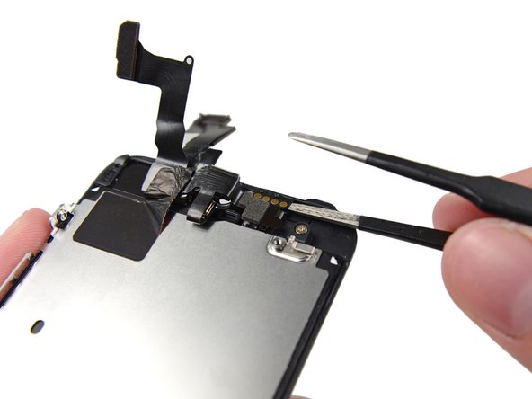 Using the edge of a set of tweezers or a metal spudger, gently pry the earpiece speaker contact cable up, to separate this portion of the camera and sensor cable from the adhesive below.