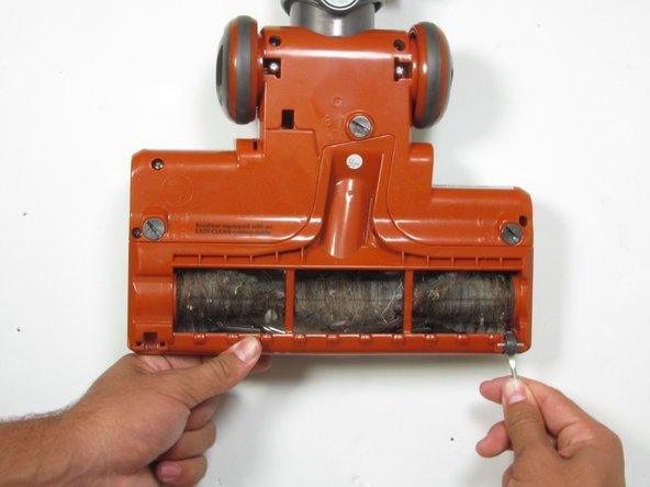 Trova e rimuovi le due piccole ruote sotto la spazzola rotante con uno strumento per fare leva in plastica.