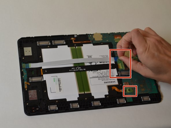 Remove the three green pieces of tape covering the white, black, and gold ribbon cables.
