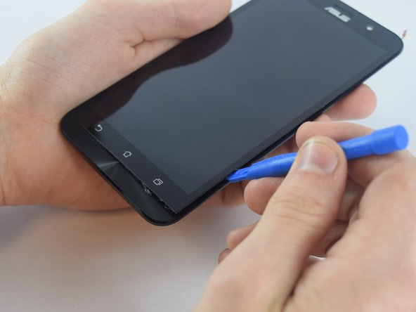 Using the plastic opening tool, pry off the display by inserting the tool in between the display and the housing at the edges of the phone.