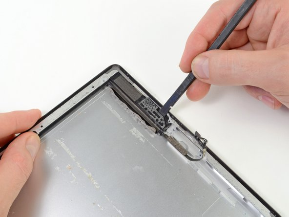 Using a spudger, carefully push the speaker assembly out of its recess in the aluminum frame.