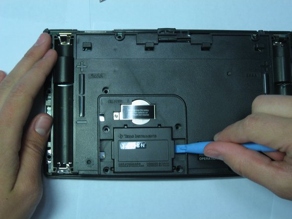 Using the Ipod Opening Tool pull up on both sides of the rectangular module while keeping the rest of the calculator flat on a surface face down