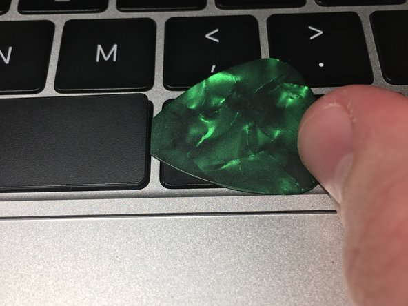 Push the pick right and down from its top. This should pull the edge of the keycap up. Make sure not to push the pick to the left (inwards, under the key) yet. If you push the pick left too early, it will end up under the scissor clip.