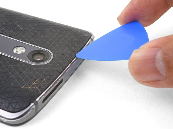 Angle an opening pick and firmly press so that it slips under the back cover.