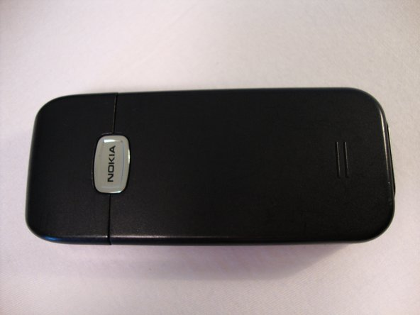 Press the grip on the back of the phone and slide the rear housing down towards the bottom of the phone.