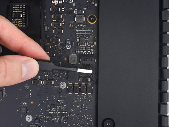 Use a pair of tweezers or your fingers to pull the right speaker cable connector straight down and out of its socket on the logic board.