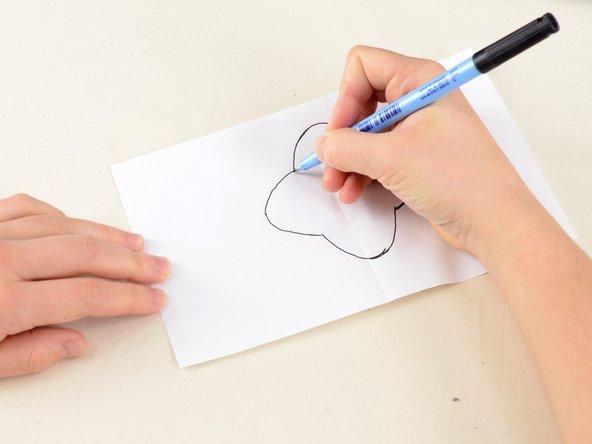 継ぎあてしたい形を紙に描きます。修理する穴よりも最低3ミリ以上大きいデザインにします。