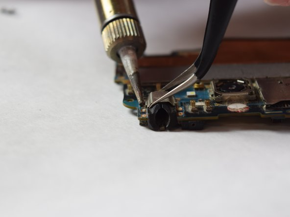 Using a soldering iron set at 400 degrees Celsius (752 degrees Fahrenheit), heat the solder joints lateral to the headphone jack. Use a pair of tweezers to lift the headphone jack from the board.