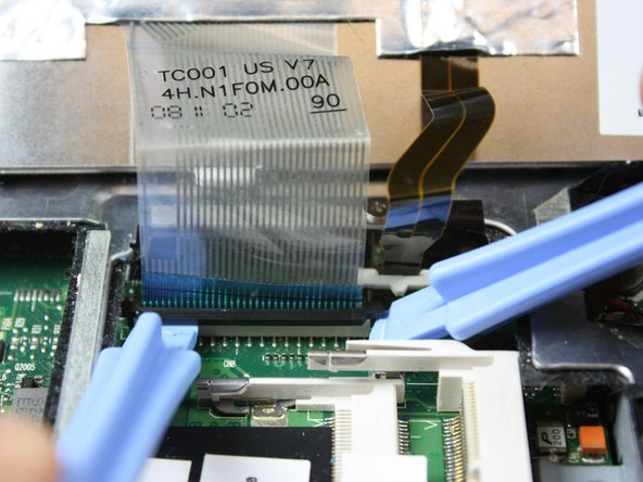 Using the plastic opening tools, pop out the ribbon cable from the rest of the computer.