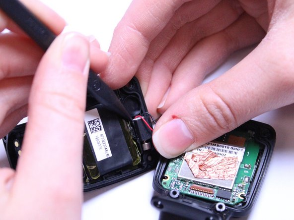 Gently wiggle the black box vibrator component away from the back panel with your fingers or a Spudger tool.