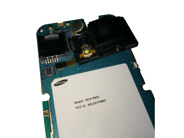Flipping the board back over, remove the speaker/rear camera by lifting from the right side as shown.