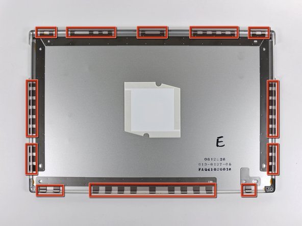 The picture at left (rear panel already removed) shows the locations of the metal clips (shown in red) that snap on to the front display bezel. In the next few steps, you will use a small flathead screwdriver to release these clips from a ridge around the perimeter of the front display bezel.