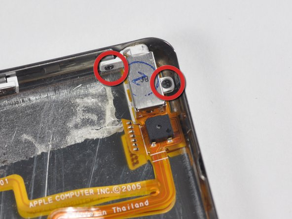 Remove the two black Phillips screws that are securing the headphone jack to the lower casing.