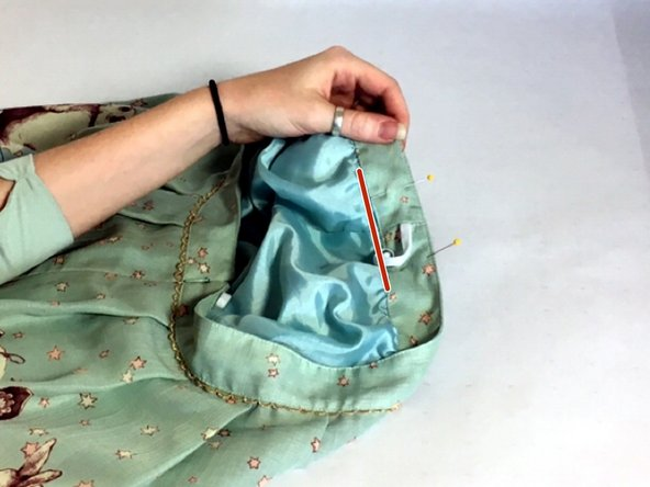 Use a seam ripper to separate the waistband from the lining in the area between your straight pins. You should also remove the seam an inch past the pins on either side.
