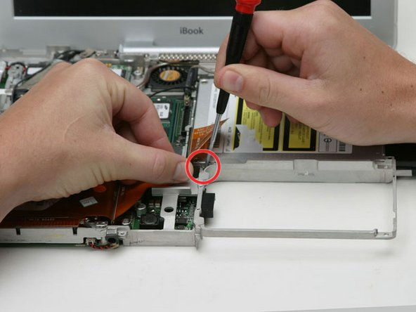 Peel back the orange ribbon cable to reveal a single Phillips screw. Remove this screw to free the optical drive from the metal framework.