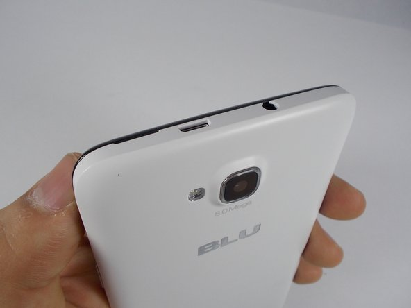In order to remove the back case, start by flipping the phone to the back side and look at it from the top.