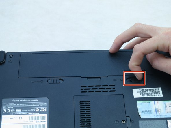 Slide the right battery bay latch to the right and hold.