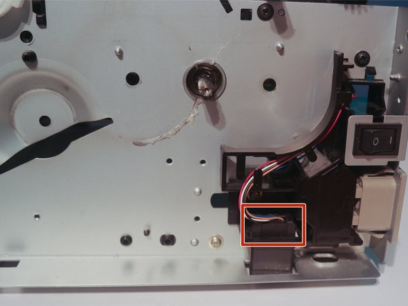 Disconnect the cable to the tray connector and route it through the hole in the chassis.
