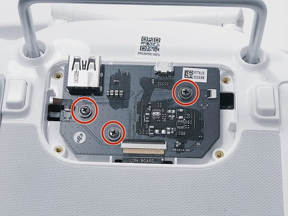 Remove three screws using a Phillips #00 screwdriver.
