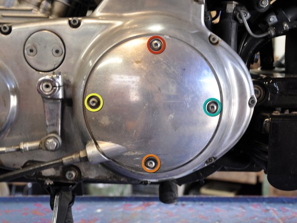 Using a T27 Screwdriver head, reinstall the clutch inspection cover. Install the screws in the following order: