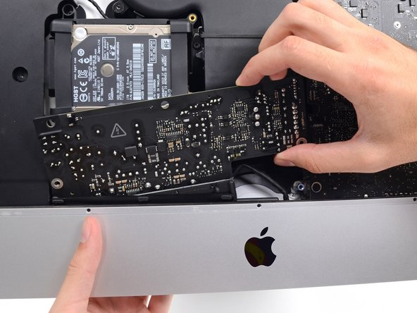 Slide the power supply to the right to clear the screw posts on the rear enclosure.