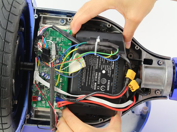 Remove the battery out of the hoverboard by lifting the battery then sliding it out from under the wires.