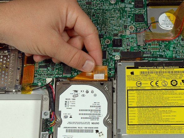 Disconnect the large orange hard drive cable from the logic board, removing tape as necessary.
