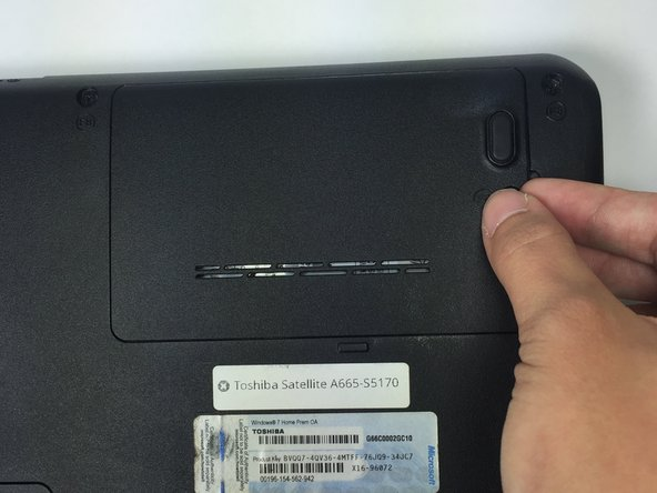 Insert something thin, such as your nail or a credit card, into the slot on the right side of the cover of the hard drive panel.