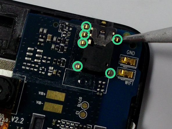 Using a soldering iron and a pair of pliers, melt the soldering connections around the headphone jack.