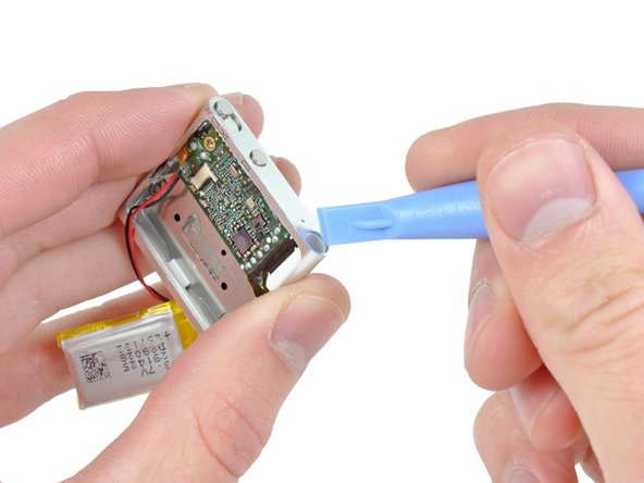 Use the edge of an iPod opening tool to push the headphone jack down toward the center of the Shuffle.