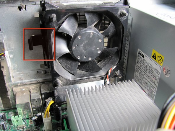 Locate the release clip on the side of the fan and hold it down with your thumb.