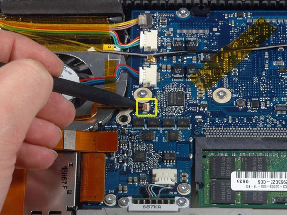 Use a spudger to flip up the brown plastic flap securing the left ambient light sensor cable to the logic board.