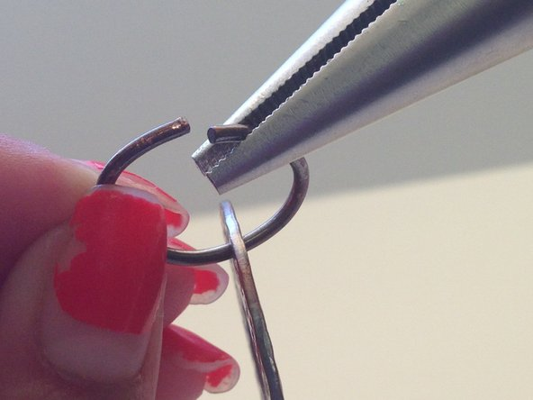 Grab one end of your chain necklace and place the pliers on the right of the small opening on the chain.