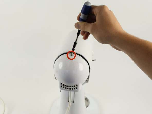 Using a Phillips #2 screwdriver, remove the 10 mm screw from the top of the back cover.