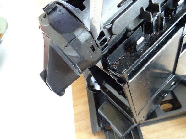 Setze einen Metallspatel zwischen den  inneren Kaffeeauslauf und die Brüheinheit und heble den Auslauf ab.