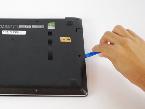 Use a plastic opening tool to gently pry the bottom of the laptop up. Slowly slide it along the edges, twisting it every so often to pop the bottom of the laptop out of the clips holding it in place.