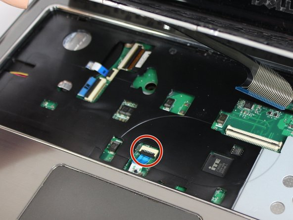 Disconnect the indicated ribbon cables underneath where the keyboard sits.